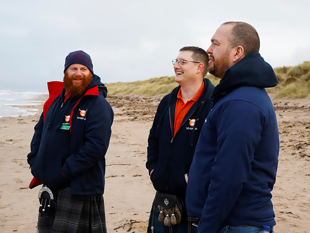 The Hairy Coo driver guides laughing on the beach